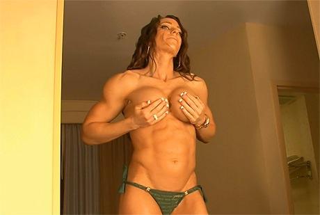 Busty sexy fitness model bikini posing and flexing